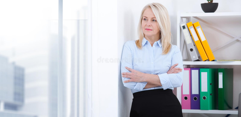 Donna di affari invecchiata bello mezzo in ufficio Donna di affari che sta vicino alla parete che guarda fuori il pensiero della  fotografia stock libera da diritti