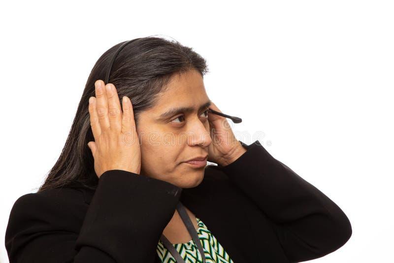Donna di affari ispana Puts On Headset per la chiamata fotografia stock