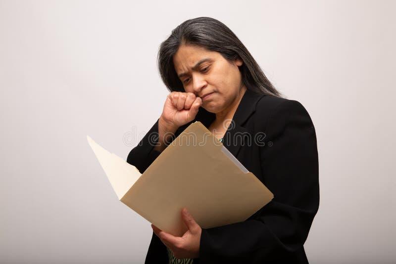 Donna di affari ispana Thinks Deep While che passa attraverso la cartella fotografie stock