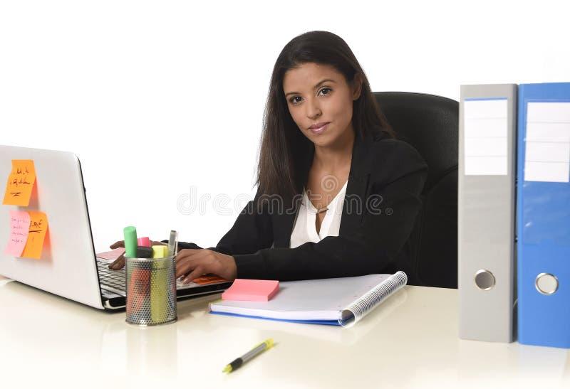 Donna di affari ispanica attraente che si siede alla scrivania che lavora a sorridere del computer portatile del computer felice immagine stock libera da diritti