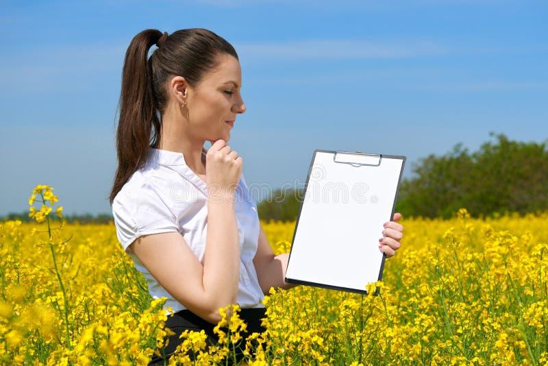 Donna di affari in lavagna per appunti colta all'aperto del giacimento di fiore Ragazza nel giacimento giallo del seme di ravizzo fotografie stock