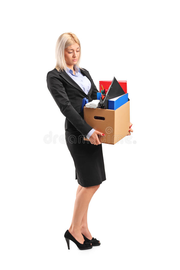 Donna di affari licenziata in un vestito che trasporta una casella immagine stock