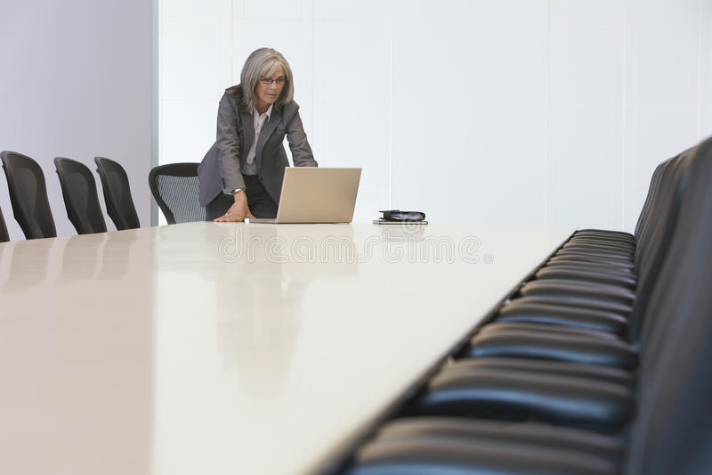 Donna di affari Looking At Laptop nella sala riunioni fotografie stock libere da diritti