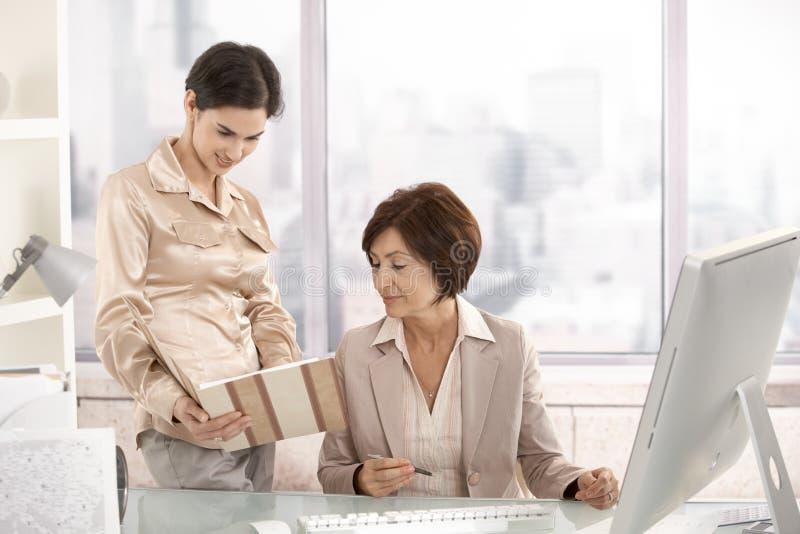 Donna di affari maggiore che lavora con l'assistente immagini stock