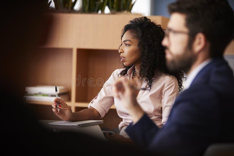 Donna di affari Making Notes Sitting alla riunione della Tabella con i colleghi in ufficio moderno fotografia stock libera da diritti