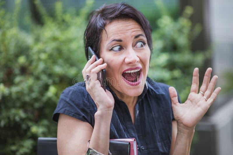 Donna di affari matura che riceve le notizie scioccanti immagini stock