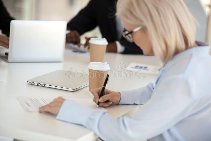 Donna di affari matura che si siede alla scrivania che firma un contratto fotografie stock