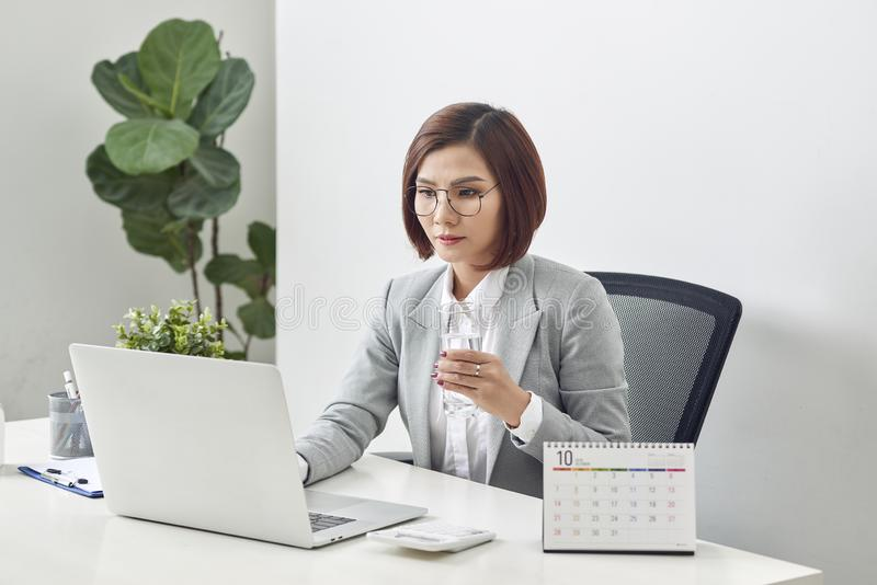 Donna di affari matura rilassata che tiene bicchiere d'acqua e che lavora al suo computer portatile nell'ufficio immagini stock
