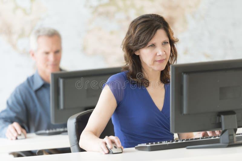 Donna di affari matura Working On Computer all'ufficio fotografie stock