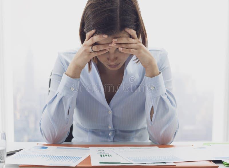Donna di affari messa a fuoco che controlla i rapporti e pensiero finanziari immagine stock