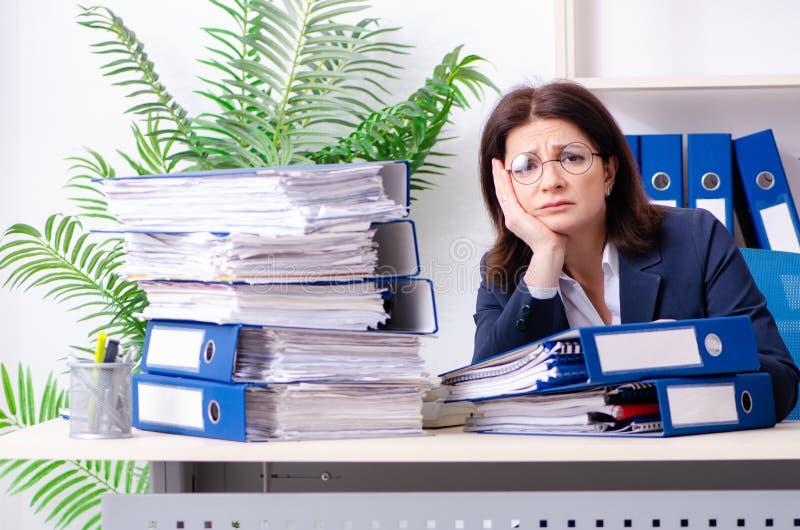 Donna di affari di mezza età insoddisfatta di eccessivo lavoro fotografia stock