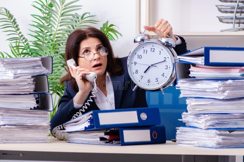 Donna di affari di mezza età insoddisfatta di eccessivo lavoro fotografia stock libera da diritti