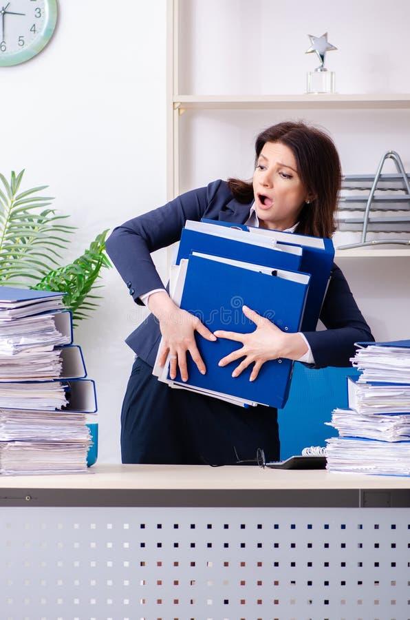 Donna di affari di mezza età insoddisfatta di eccessivo lavoro immagine stock