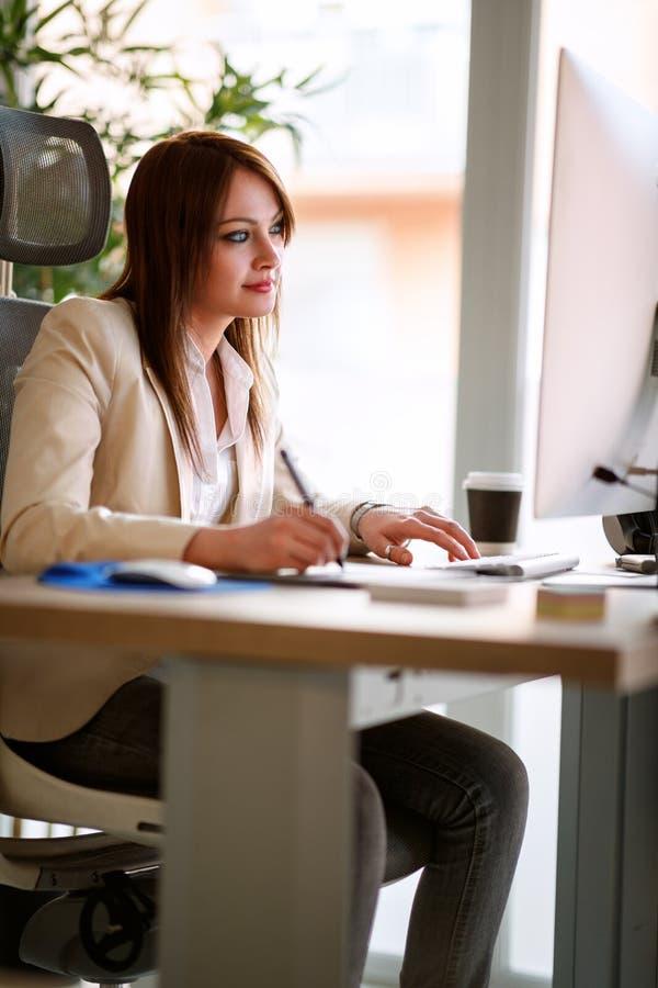 Donna di affari moderna che assorbe ufficio fotografie stock libere da diritti
