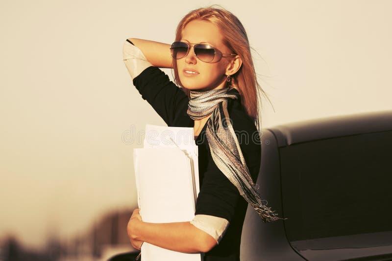 Donna di affari di modo con le carte finanziarie accanto alla sua automobile immagini stock