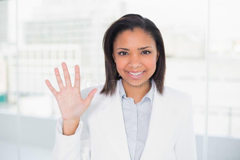 Donna di affari mora abbastanza giovane che ondeggia la sua mano immagine stock