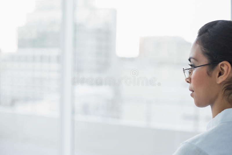 Donna di affari mora adorabile che si siede nell'ufficio luminoso immagine stock libera da diritti