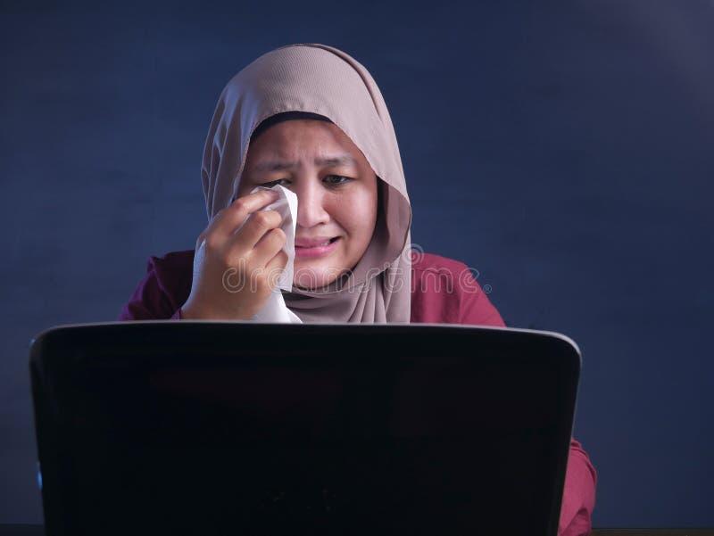 Donna di affari musulmana gridante triste per vedere cattivo rapporto di perdita finanziaria sul computer portatile fotografia stock libera da diritti