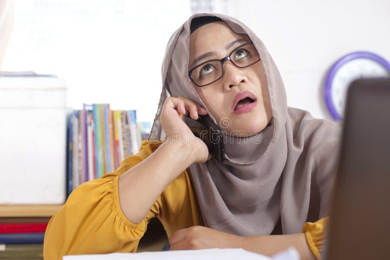 Donna di affari musulmana pigra stanca Waiting For News sul telefono nell'ufficio fotografia stock libera da diritti