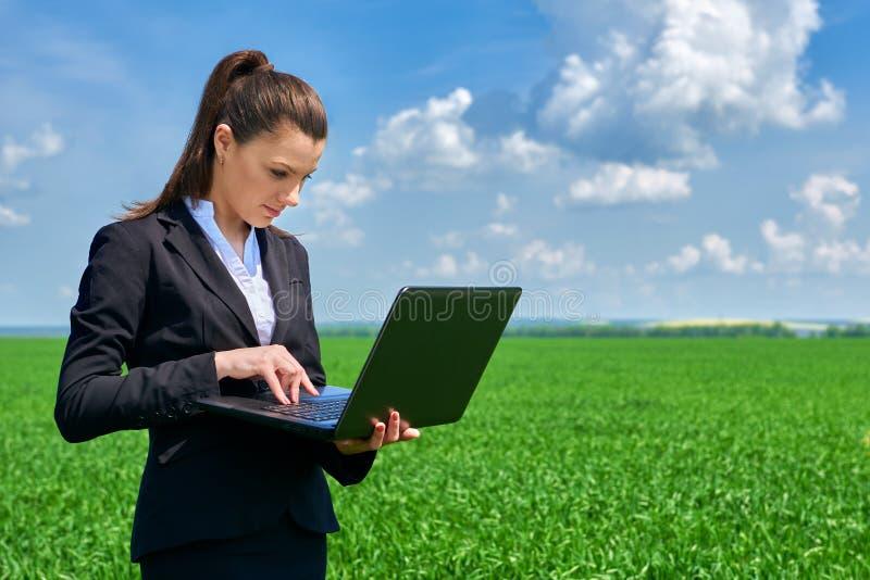 Donna di affari nel lavoro all'aperto del campo di erba verde sul computer portatile Ragazza vestita in vestito nero Bello paesag immagine stock libera da diritti