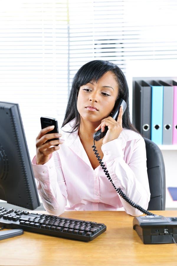 Donna di affari nera che per mezzo di due telefoni allo scrittorio fotografia stock libera da diritti
