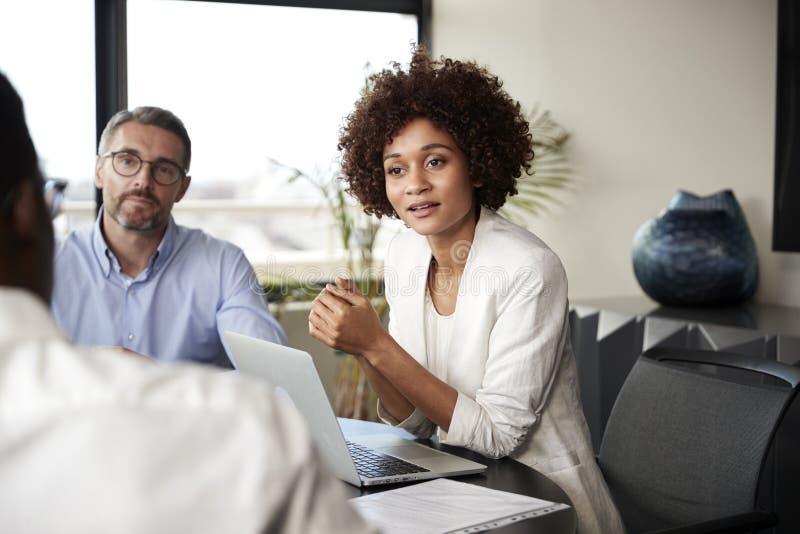 Donna di affari nera millenaria che ascolta i colleghi ad una riunione d'affari corporativa, fine su fotografia stock libera da diritti