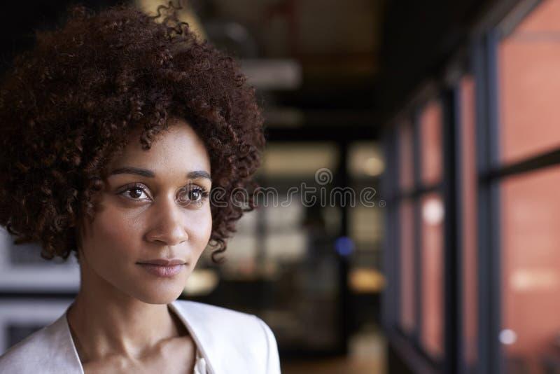Donna di affari nera millenaria che guarda dalla finestra in un ufficio, di gran lunga, fine su fotografia stock libera da diritti
