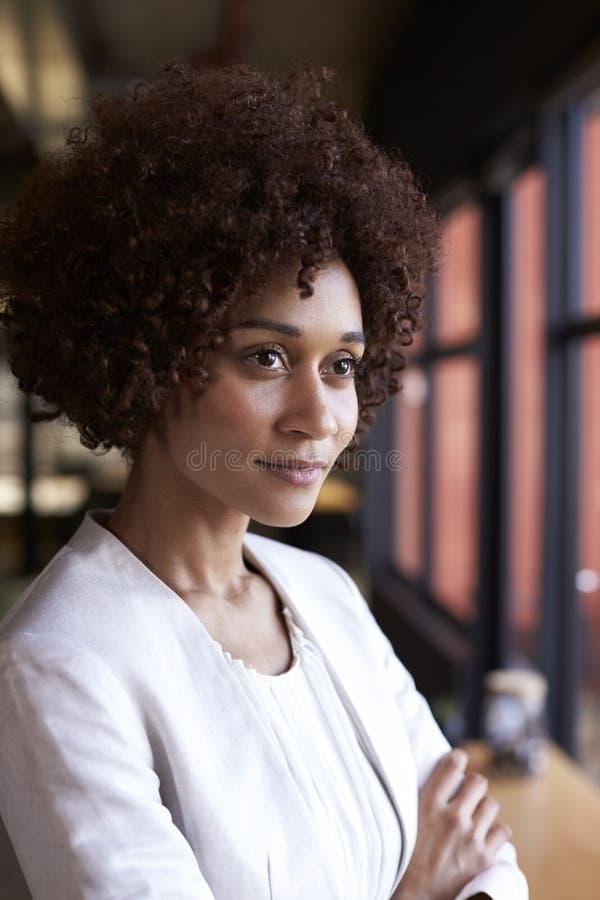 Donna di affari nera millenaria che guarda dalla finestra in un ufficio, vita su, verticale fotografie stock libere da diritti
