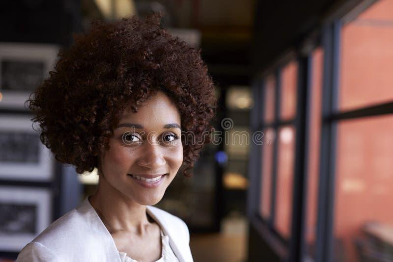 Donna di affari nera millenaria che sorride alla macchina fotografica dalla finestra in un ufficio, fine su immagini stock libere da diritti