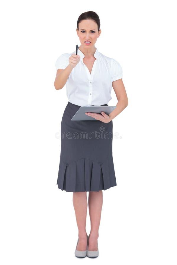 Donna di affari nervosa che indica alla macchina fotografica fotografia stock