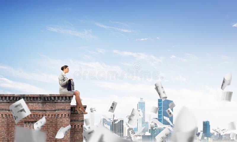 Donna di affari o ragioniere sul tetto del mattone contro lo scape moderno della citt? fotografia stock