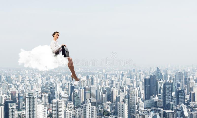 Donna di affari o ragioniere sulla nuvola che galleggia su sopra la citt? moderna fotografia stock libera da diritti