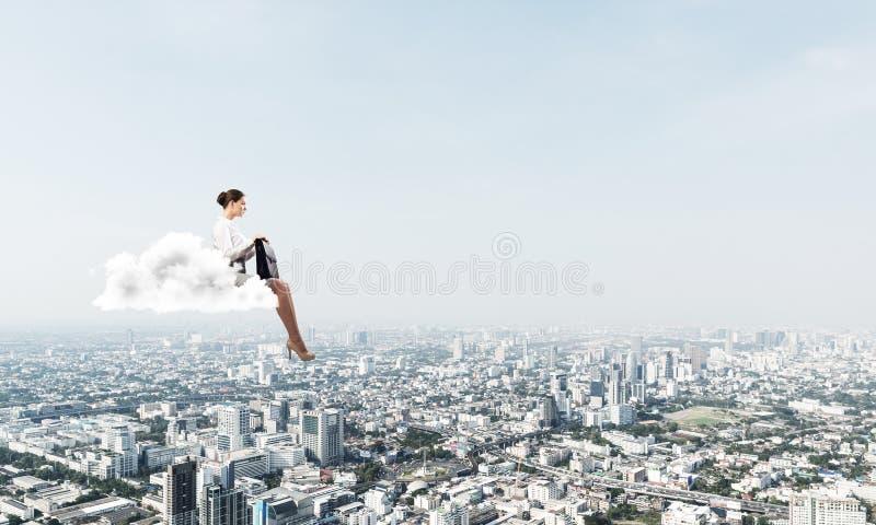 Donna di affari o ragioniere sulla nuvola che galleggia su sopra la citt? moderna fotografia stock