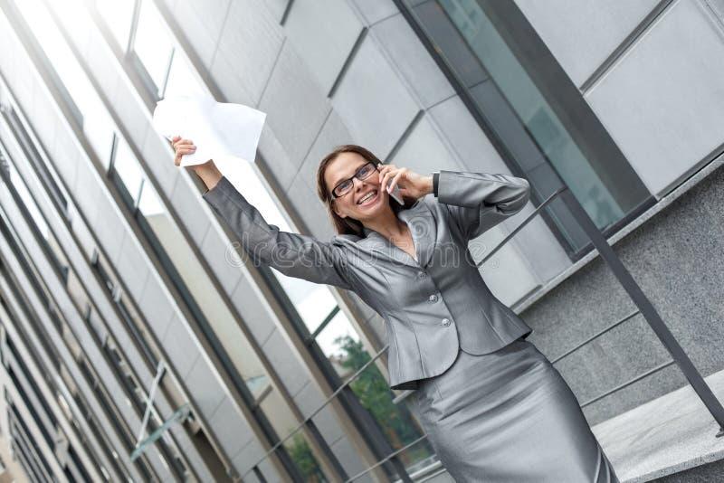 Donna di affari in occhiali che stanno sulla mano di risposta di chiamata della via della città su con il contratto allegro fotografia stock