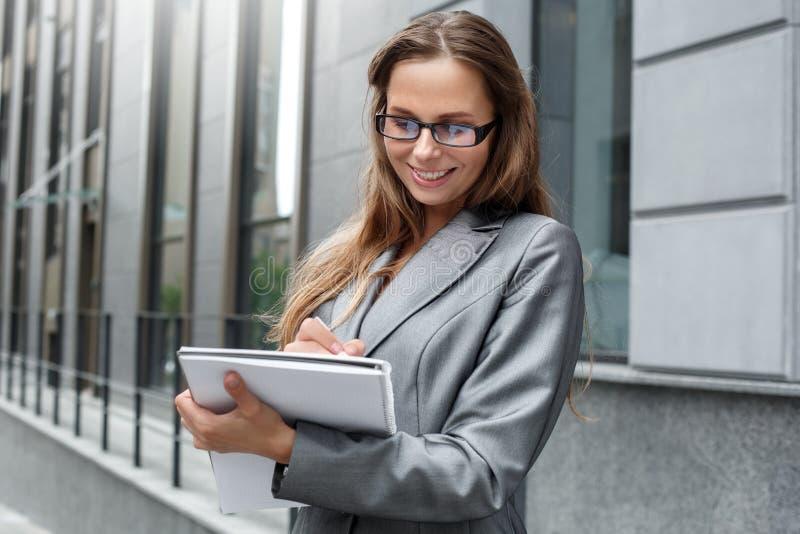 Donna di affari in occhiali che stanno sulla via della città che prende le note nel sorridere del giornale allegro fotografie stock