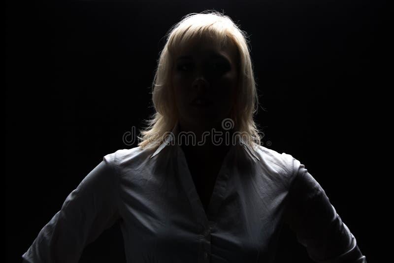 Donna di affari in ombra che esamina macchina fotografica fotografia stock libera da diritti