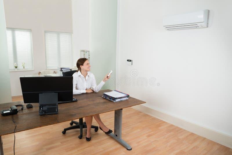 Donna di affari Operating Air Conditioner in ufficio immagini stock