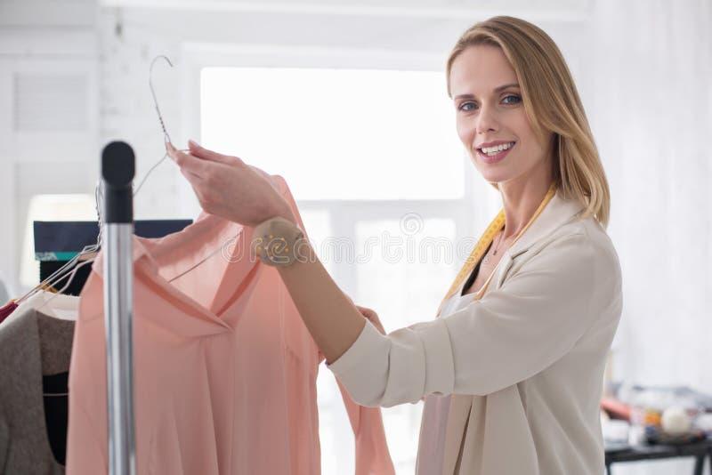 Donna di affari ottimista allegra che possiede sala d'esposizione immagine stock