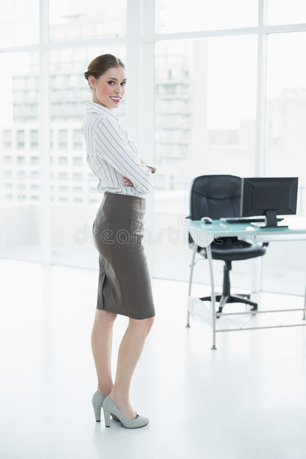 Donna di affari pacifica attraente che posa stare nel suo ufficio immagini stock