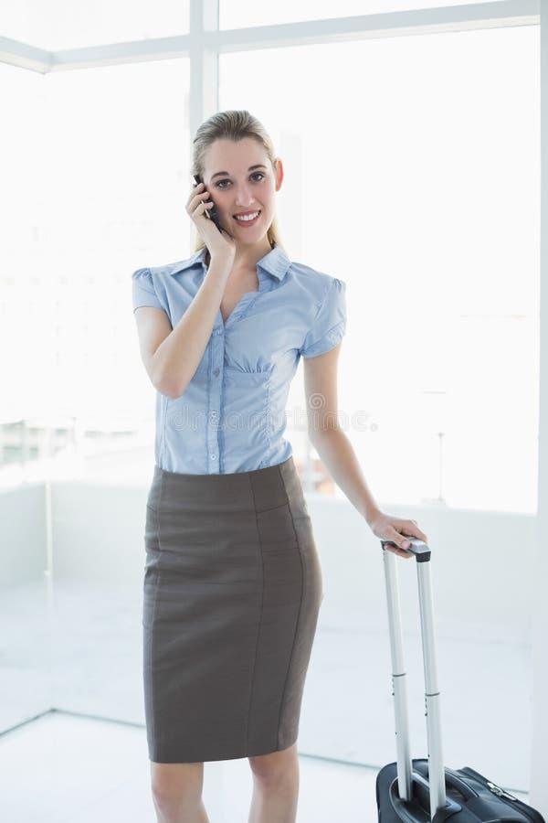 Donna di affari pacifica splendida che telefona mentre stando nel suo ufficio immagine stock