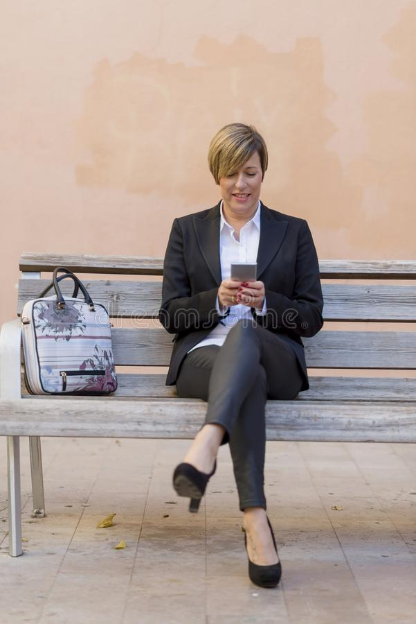 Donna di affari On Park Bench che per mezzo del telefono cellulare fotografia stock
