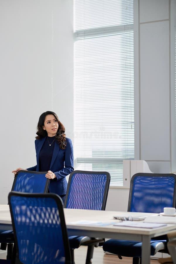 Donna di affari pensierosa alla sala del consiglio moderna immagini stock