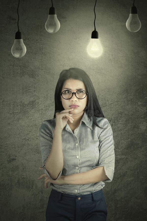 Donna di affari pensierosa sotto una lampadina luminosa fotografia stock libera da diritti
