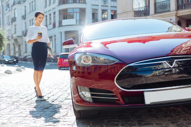 Donna di affari piacevole astuta che si avvicina alla sua automobile immagini stock