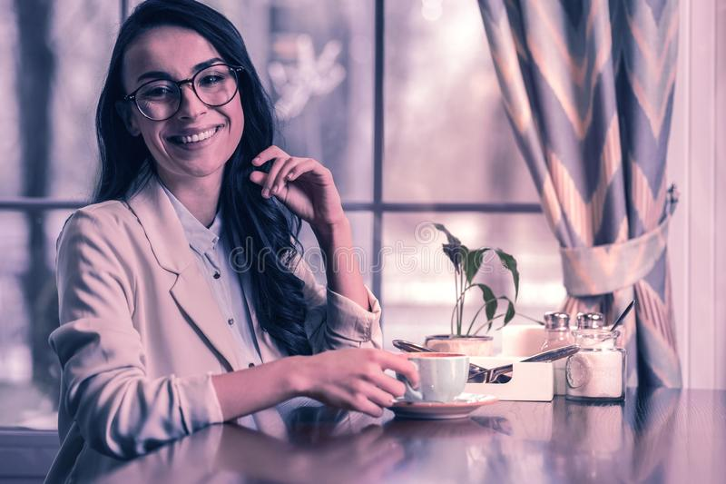 Donna di affari positiva allegra che è nel caffè fotografia stock libera da diritti