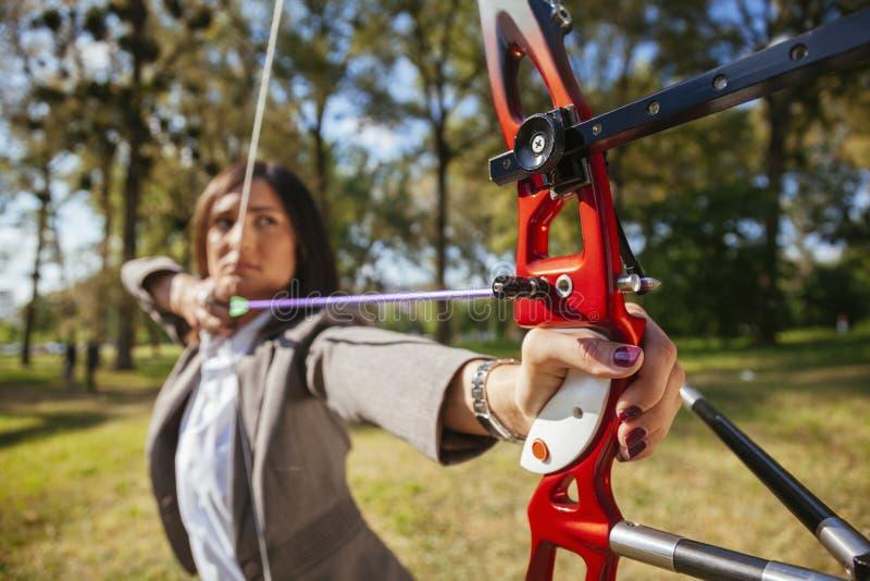 Donna di affari Practicing Archery immagini stock
