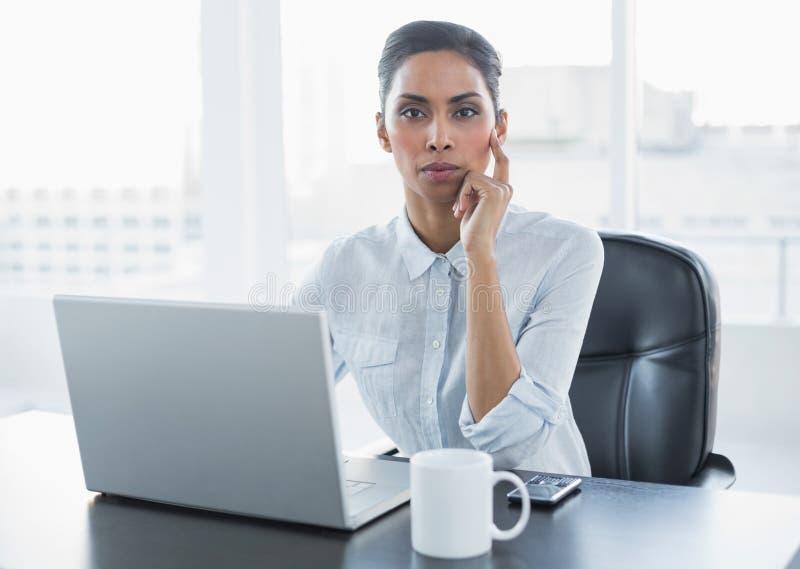 Donna di affari premurosa attraente che si siede al suo scrittorio immagini stock libere da diritti