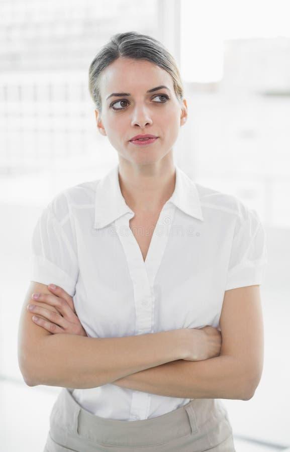 Donna di affari premurosa che posa nel suo ufficio immagini stock libere da diritti