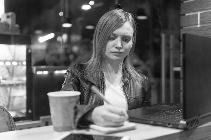 Donna di affari, ragazza che tiene una penna, scrivente in un taccuino, computer portatile in caff?, smartphone, penna, computer  immagini stock libere da diritti