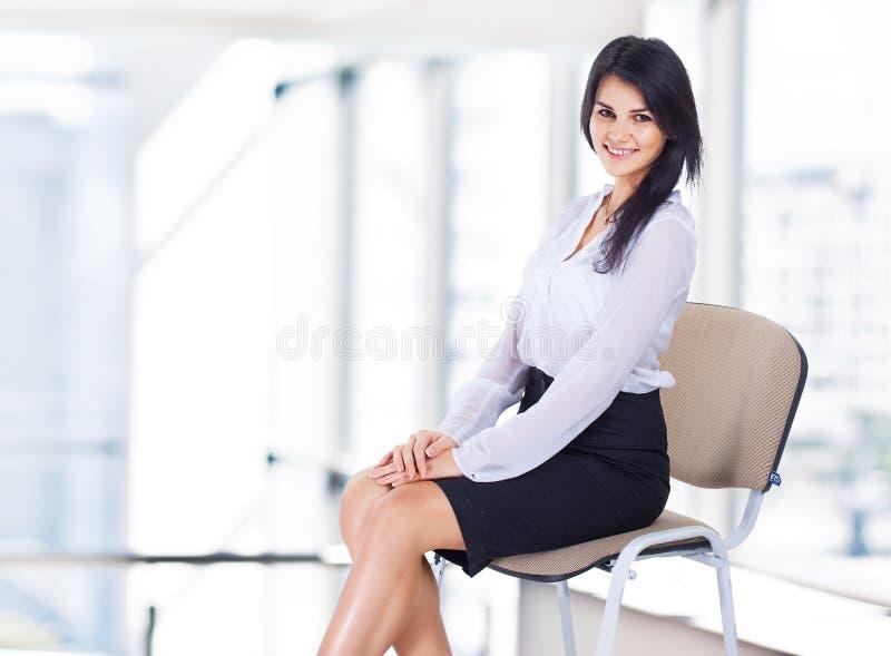 Donna di affari, sedentesi su una sedia fotografia stock libera da diritti